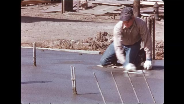 1950s: Man operating crane. Man smoothing cement.