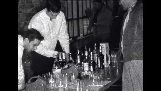 1950s: Man waits at bar as bartenders drop ice cubes into glasses. Bartender grabs beer, removes cap, hands it to man, grabs another and hands to black man with plate of food.