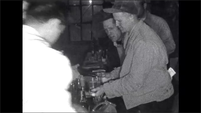 1950s: Bartenders are busy behind bar, making drinks, opening bottles. A line of men wait for drinks. Bartender pours out of two bottles into outstretched glasses of men in line.
