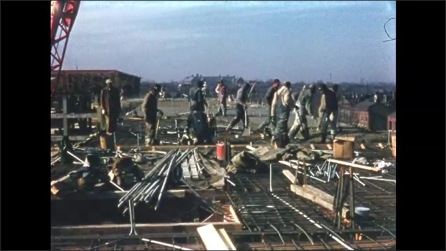 1950s: Workers on roof of building, cement drops from chute, crane lifts chute.