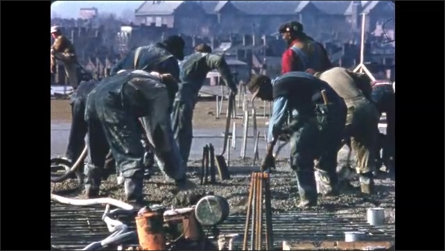 1950s: Workers at construction site. Men shoveling cement. Men walking, man carrying broom.