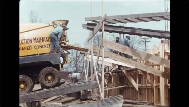 1950s: Workers on construction site with cement truck. Closer view of men working. Man on truck. Men working.