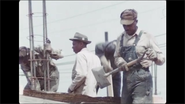 1950s: Men working on construction site.