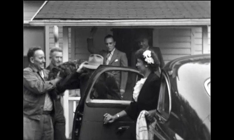 1940s: Men gather on porch near car and watch woman exit house. Man holds cat near head of man near car. Men laugh and shake hands. Men and woman gather at car.