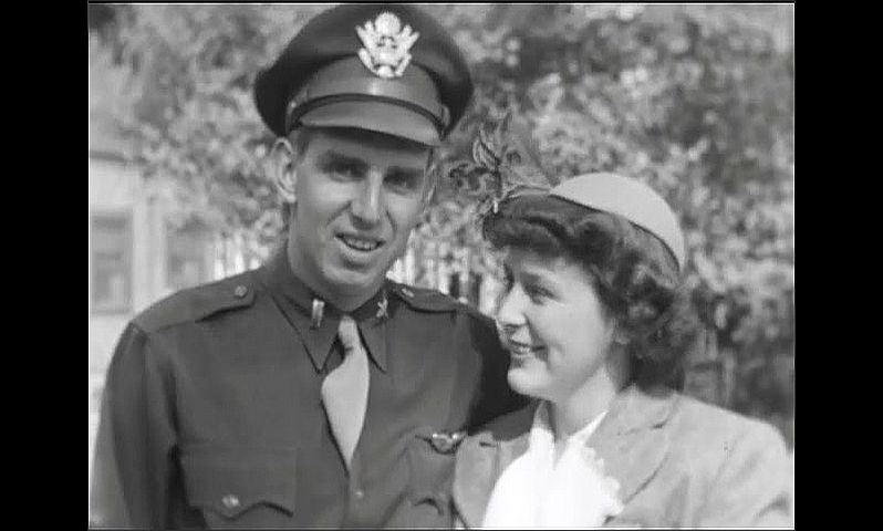 1940s: Police officer and woman hold hands and walk on sidewalk. Man in uniform poses and talks with woman. Water ripples on large wooded lake.