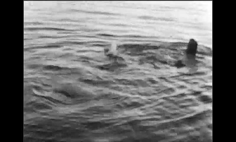 1940s: Man wades into and swims in lake. Man exits house and waves. Man walks off porch.