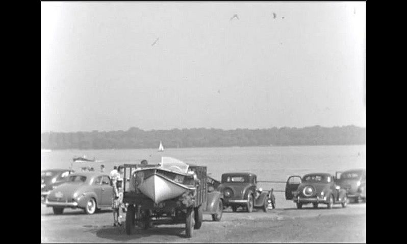 1940s: People walk by cars and boats at lakeshore boat launch. Boats speed along lake near parking area. Men and women walk around lakeshore parking and launch area.
