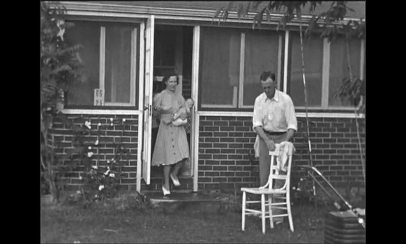 1940s: Man opens door of home and removes wooden chair. Woman and baby walk from door of home. Woman and baby sit on chair. Girl in swimsuit stands in doorway and speaks.