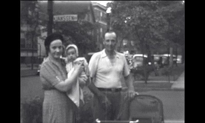 1940s: Man and woman pose with baby in city park.
