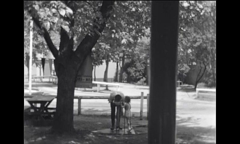 1940s: Men walk past picnic tables and cabins in park. Men and child drink from public water fountain in park. House with porch on wooded lawn.