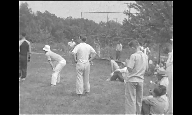 1940s: People watch as men and boys play baseball in public park.