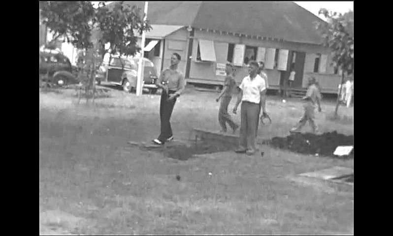 1940s: Man with arm around two women walks by parking lot. Men toss horseshoes in park.