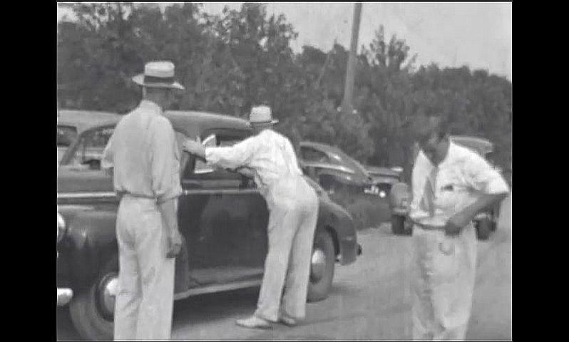 1940s: Man points and gives direction to driver of car on road. Men gather in street near cars.