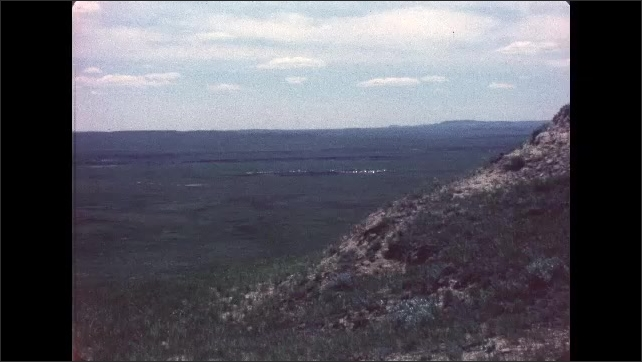 1970s: UNITED STATES: view across landscape. Plains and rocky ground. Man on horse moves herd of cows