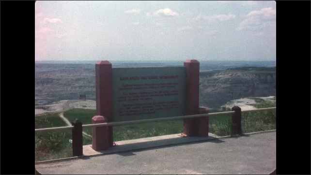 1970s: UNITED STATES: sign at view point. Lady films view. Canyon view