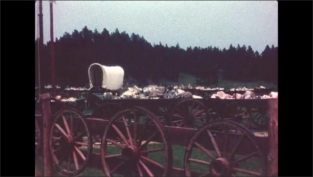 1970s: UNITED STATES: cowboy carts in landscape. American flag by camp. Caravans and carts.