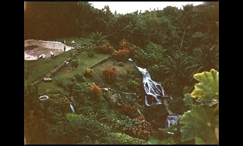 1950s: Jamaica. Verdant landscape with waterfalls, palm trees and lush grass overlooking the ocean. Water flowing over rocks. Middle aged woman in green dress dusts off shoes next to waterfall.