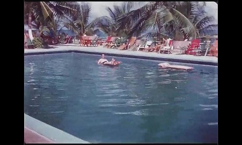 1950s: Jamaica. Tropical beachside resort. Man floats in swimming pool, leans back to puts hands behind head and nearly loses balance. Palm trees and lounge chairs around the pool.
