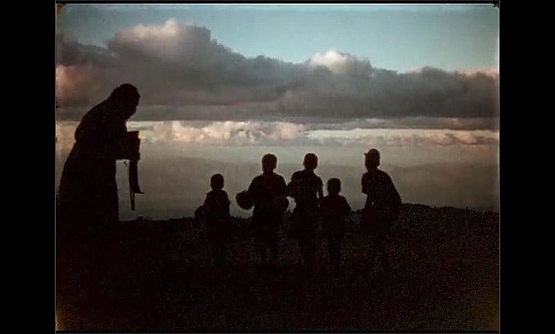 1950s: Jamaica. Five young Jamaican boys dance against a backdrop of clouds, some holding balls. A woman beckons them closer and takes photgraphs of them.