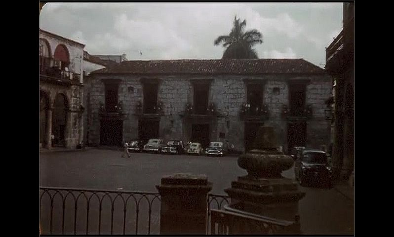 1950s: Jamaica. Men walk around a town square with an old stately church. A different building in town with stone arches. Overlooking a town from a hill.