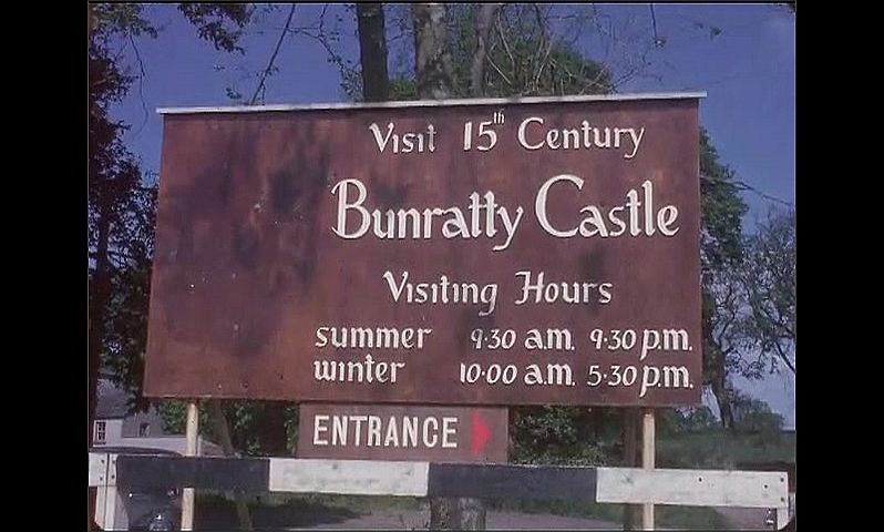 1950s: Flag waves in wind on pole on top of castle. Sign for Bunratty Castle. Sign for Shannon Shamrock Inn.