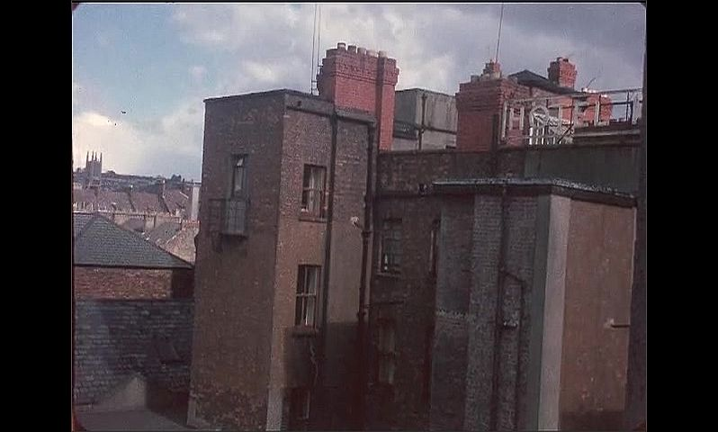 1950s: Roofs of buildings across city. Sunlight shines on side of building. Sign for The Old Castle.