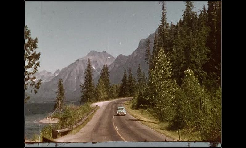 1950s: UNITED STATES: car drives along road in mountains. Lake side road