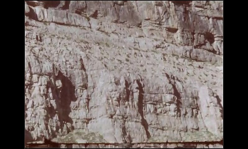 1950s: UNITED STATES: rock face on mountain side. Layers of rock. Snow on mountain. Man by lake. Men attach supplies on horse back. Men tie load with ropes.