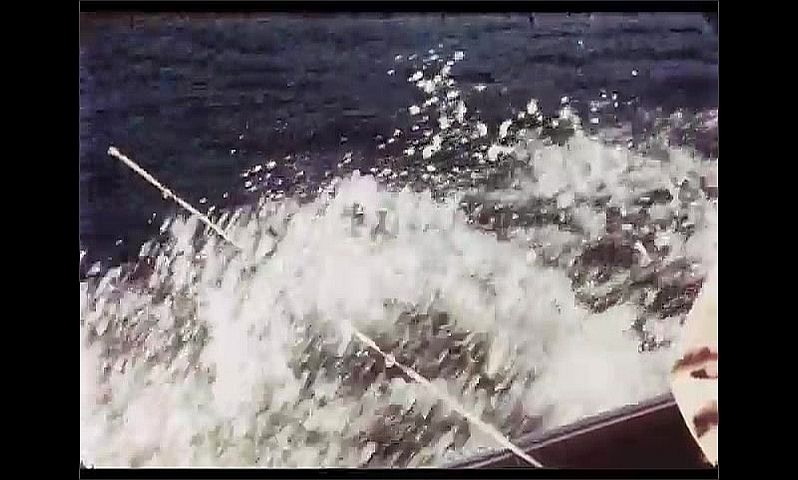 1970s: CANADA: wake around motor boat on water. Rod in edge of boat.