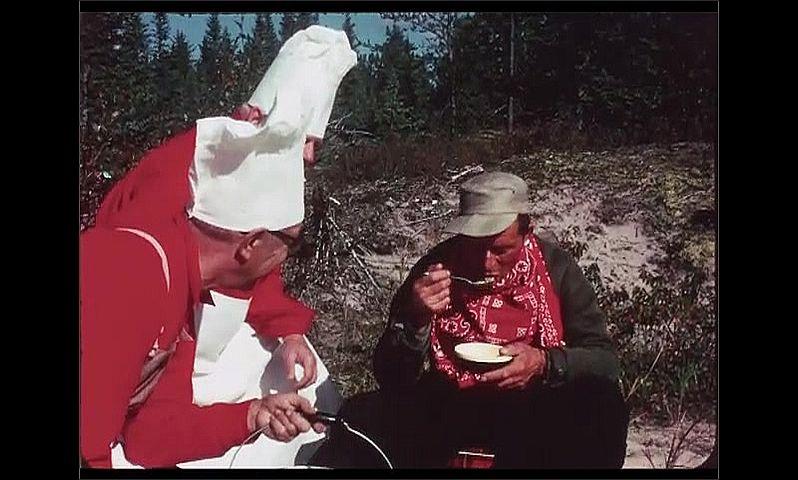 1970s: CANADA: man tries food from bowl. Men on beach by lake. Man tastes food. Man smiles