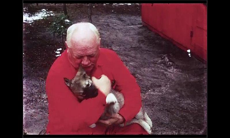 1970s: CANADA: man cuddles puppy dog by cabin. Man strokes puppy.