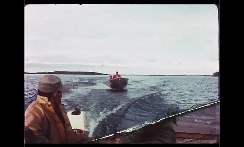 1970s: CANADA: men on boat with motor. Wake behind boats. Men hang fish from wood.