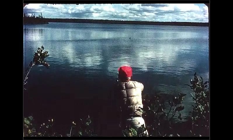 1970s: CANADA: man fishing by lake shore. Man casts off. Man smokes pipe while fishing