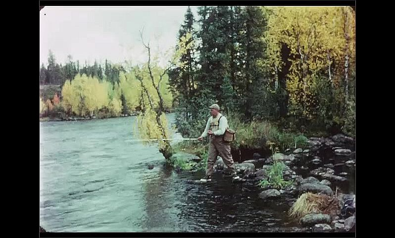 1970s: CANADA: man casts off from side of river. Man balances on rocks by water