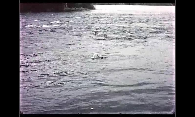 1970s: CANADA: fish on line splashes in water. Man pulls in catch.