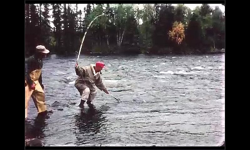 1970s: CANADA: man lifts fish from water in net. Man bends towards water. Man smokes pipe.