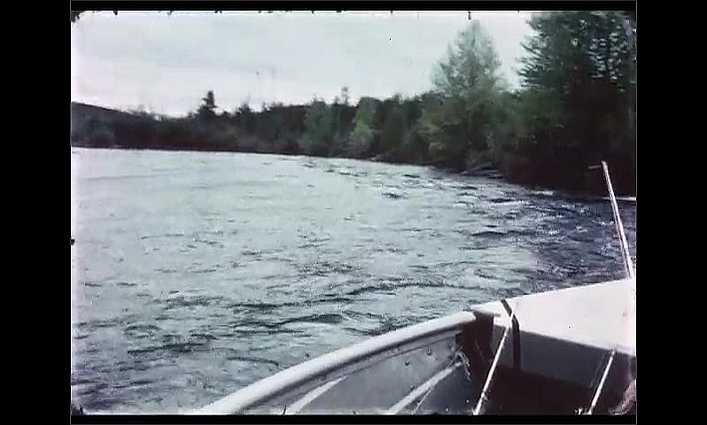 1970s: CANADA: boat travels up river and rapids. Man smokes pipe on boat. Man lies on boat.