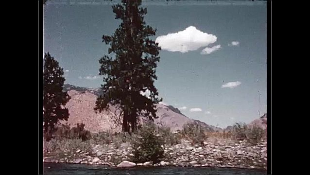 1950s: a boat floating down a river in front of mountains before reaching rock-infested rapids