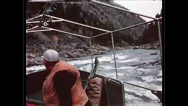 1950s: boat going through a section of rapids, a section of calm river behind the boat
