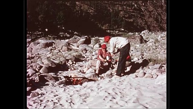 1950s: men sit around cooking fire and are served something from a pot