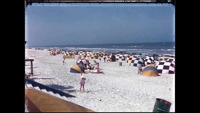 1950s: UNITED STATES: wind shelters on beach. Lady walks on sand. People on beach by ocean. Children play in sand