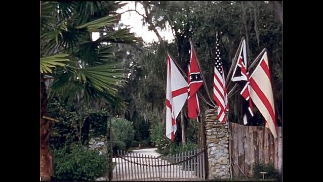 1950s: UNITED STATES: Sign for Lost Mission and Olde English Sugar Mill. Park Here sign. Flags by entrance. Old mill.