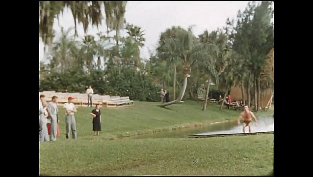 1950s: UNITED STATES: synchronised water ski show. Water skier on grass. People on beach by hotel.
