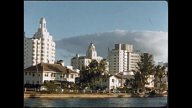 1950s: UNITED STATES: boat travels along water. View of hotel buildings and homes by waterfront. Road by water.