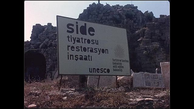 1950s: Ancient ruins. Sign at site of ruins. Water and mountain.
