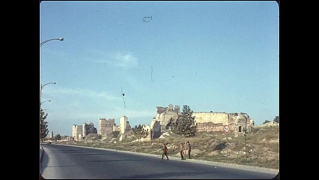 1950s: Man walks along roadside, ruins in background. Man crosses the street, stops in the middle of the street.