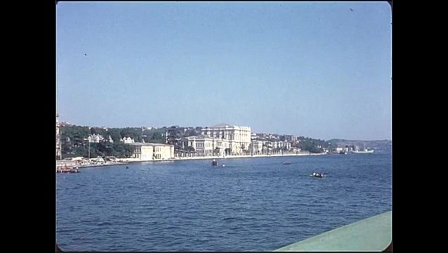 1950s: Boats in water. Large building on banks of water.