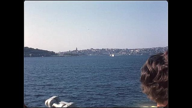 1950s: Person stands on boat, boat travels across water. City along coast.
