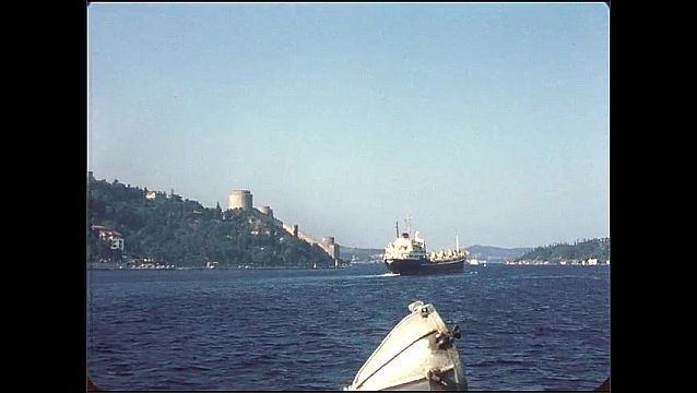 1950s: Boat travels across water. Large palace on water. Stone wall on hillside.