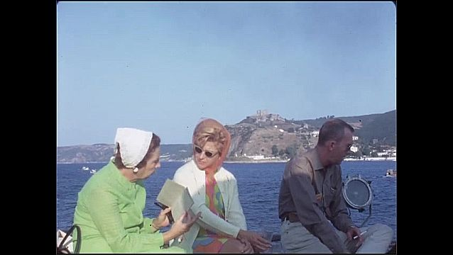 1950s: People sit on boat. Man smokes cigarette. Women talk. Turkish flag on top of round stone tower.